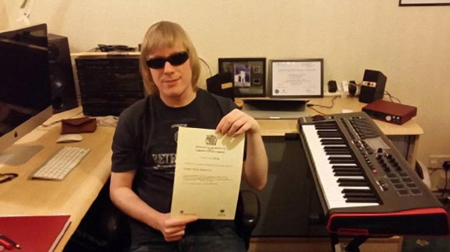 David Shervill in his music studio holding his certificate